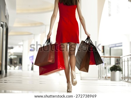 Beautiful young woman in a red dress, holding shopping bags walking in the shop - stock photo