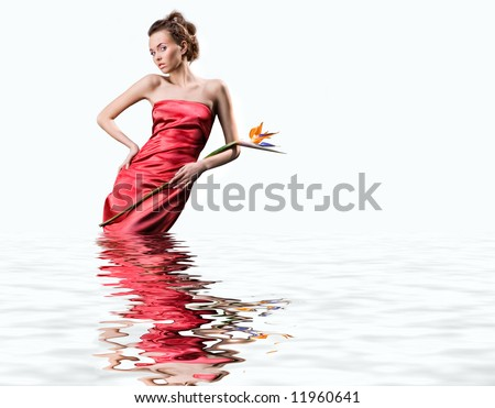 Beautiful young woman in a  red dress stands in the water. Holds an exotic flower in a hand - stock photo