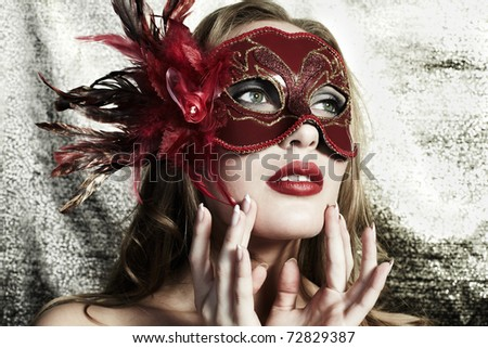 Beautiful young woman in a red mysterious venetian mask on a gold background - stock photo