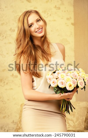 Beautiful young woman in a room holds a bouquet of roses. Beauty, fashion. - stock photo