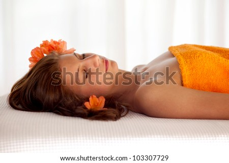 Beautiful young woman in a state of total relaxation and well being lying with her eyes closed on a spa table draped in an orange towel with orange blossoms in her hair