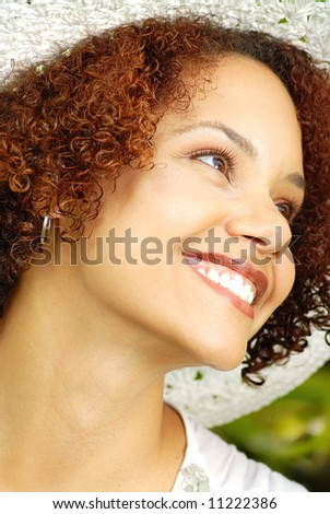 Beautiful young woman in a summer hat laughing outdoors - stock photo