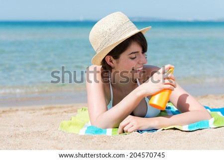 Beautiful young woman in a trendy straw hat applying suntan lotion spraying it onto her skin as she relaxes on a tropical beach sunbathing on her towel on the sand - stock photo