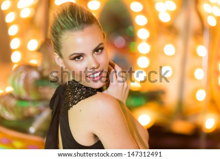 Beautiful young woman in a venue with party lights dressed in a stylish sexy black dress looking back over her shoulder at the camera with a smile - stock photo