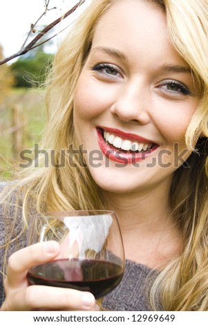Beautiful young woman in a vineyard drinking wine - stock photo