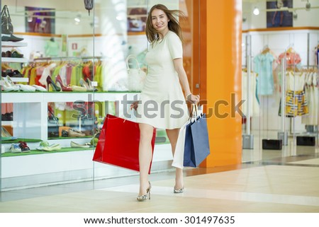 Beautiful young woman in a white dress, holding shopping bags walking in the shop - stock photo