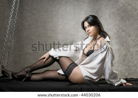 Beautiful young woman in a white man's shirt and black stockings. - stock photo