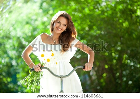 Beautiful young woman in a white summer dress and daisies in her hand clinging to an old bicycle handlebars - stock photo
