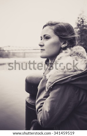 Beautiful young woman in a winter jacket, with brown hair and brown eyes, leaning on a post, staring out thoughtfully at the River Tyne.  The Queen Elizabeth II Metro Bridge is in the distance. - stock photo