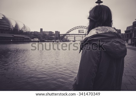 Beautiful young woman in a winter jacket, with brown hair and brown eyes, leaning on a post, staring out at the River Tyne.  Tyne Bridge and Sage Gateshead in distance. - stock photo