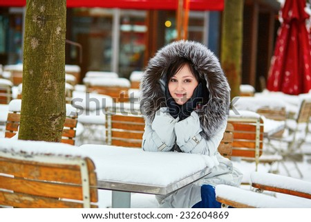 Beautiful young woman in an outdoor cafe enjoying rare snowy winter day in Paris