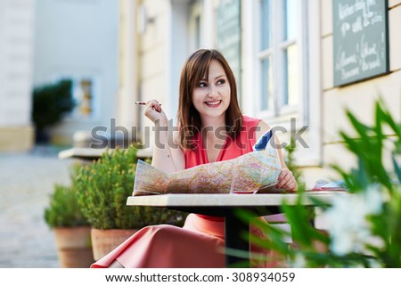Beautiful young woman in an outdoor cafe using map and planning itinerary in Vienna, Austria - stock photo