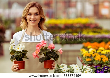 Beautiful young woman in apron is holding plants, looking at camera and smiling while standing in orangery