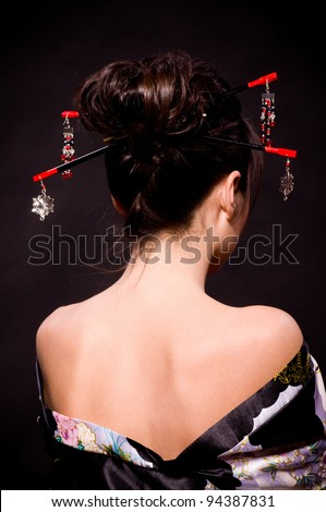 Beautiful young woman in Asian costume on black background. - stock photo