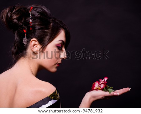 Beautiful young woman in Asian costume with red flowers on black background. - stock photo