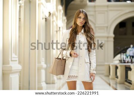 Beautiful young woman in autumn coat walking in the shop - stock photo