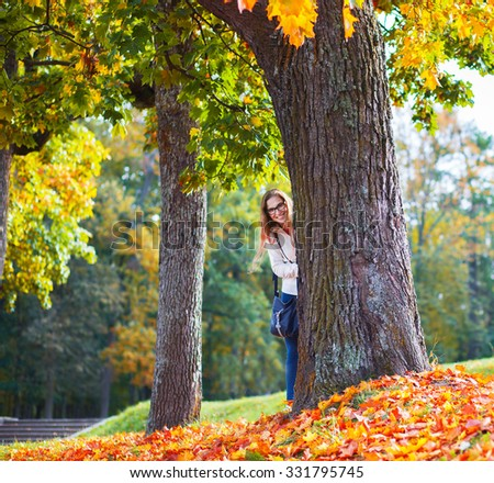 beautiful young woman in autumn park hiding behind a tree - stock photo