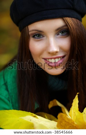 Beautiful young woman in autumn park. Shallow DOF. - stock photo