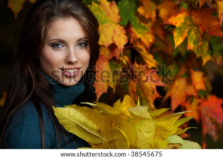 Beautiful young woman in autumn park. Shallow DOF.