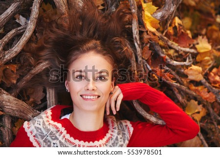 Beautiful young woman in autumn park. Top view