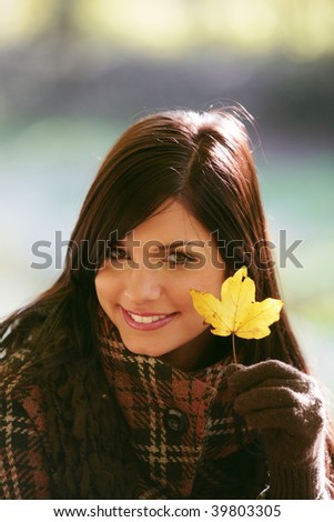 Beautiful young woman in autumnal park - stock photo