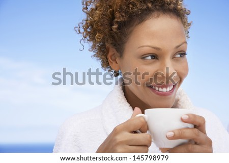 Beautiful young woman in bathrobe having coffee outdoors - stock photo
