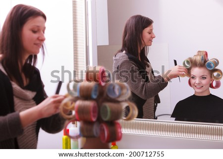 Beautiful young woman in beauty salon. Blond girl with hair curlers rollers by hairdresser. Hairstyle. Reflection in mirror. - stock photo