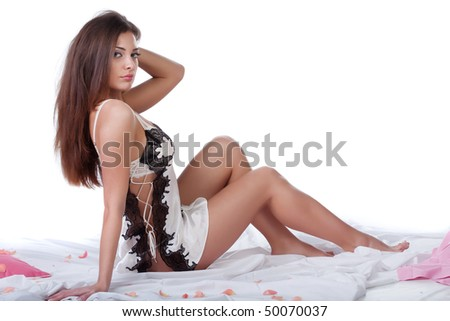 Beautiful young woman in bed isolated on white