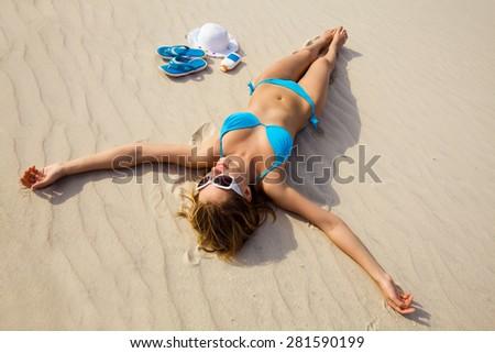 beautiful young woman in bikini lying and sunning on the beach - stock photo