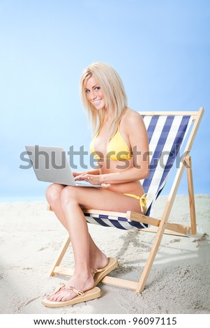 Beautiful young woman in bikini lying on a deckchair using laptop at the beach - stock photo