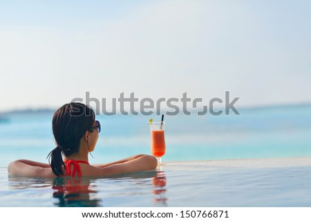 Beautiful young woman in bikini lying on a deckchair with a drink by the sea - stock photo