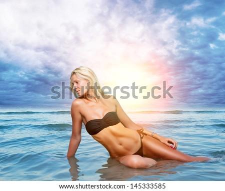Beautiful young woman in bikini on the beach.  - stock photo
