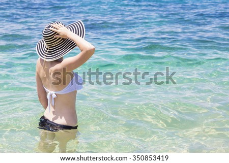 Beautiful young woman in bikini on the sunny tropical beach - stock photo