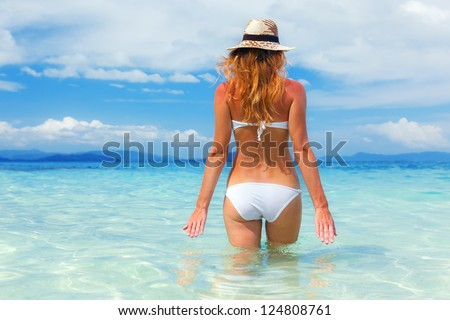 Beautiful young woman in bikini on the sunny tropical beach relaxing in water - stock photo