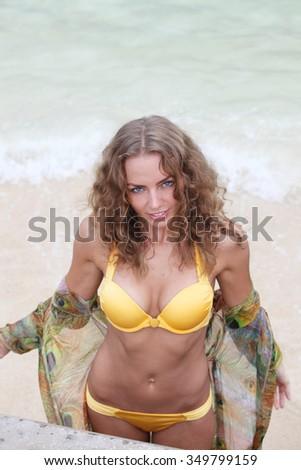 Beautiful young woman in bikini on tropical sea beach - stock photo