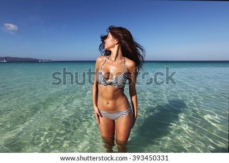 Beautiful young woman in bikini posing in sea and waving hair - stock photo