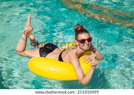 Beautiful young woman in bikini Relaxing in a pool in summer and having fun - stock photo