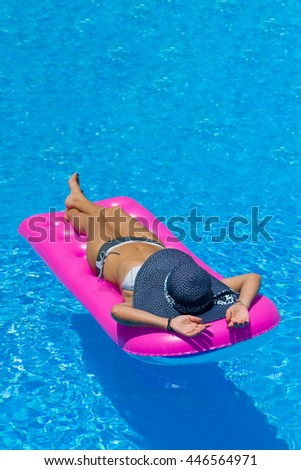Beautiful young woman in bikini Relaxing in a swimming pool