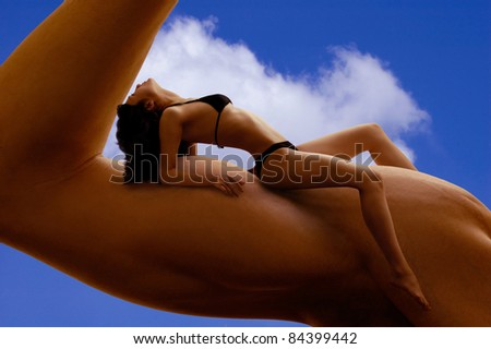 Beautiful young woman in bikini resting on a man's biceps. Fitness, tanning, health and beauty concept. - stock photo