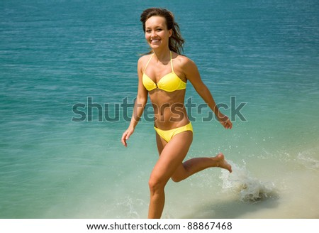 beautiful young woman in  bikini runs and smiles on the edge of water at the seaside resort - stock photo