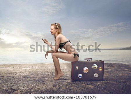 Beautiful young woman in bikini sitting on a suitcase and using a mobile phone