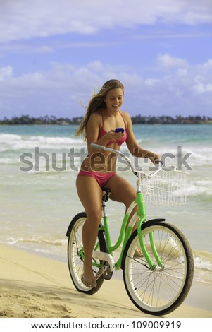 beautiful young woman in bikini texting on her cell phone at the beach with her bike - stock photo