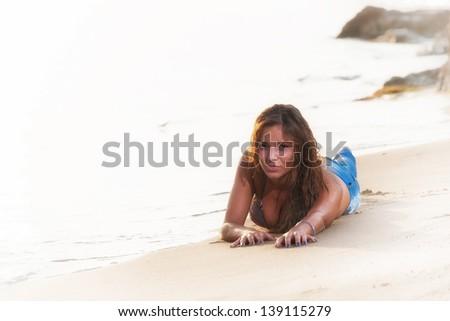Beautiful young woman in bikini top and jeans on the beach - stock photo