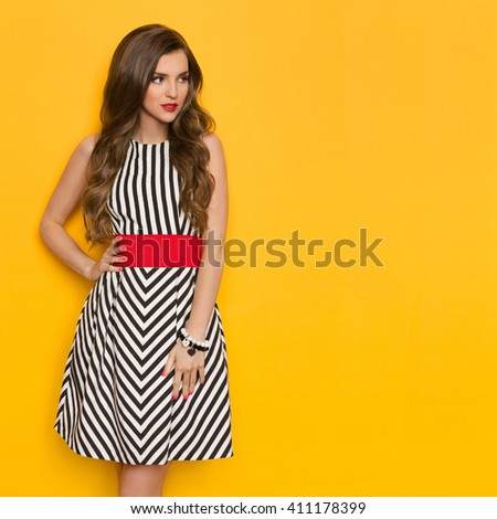 Beautiful young woman in black and white striped dress posing with hand on hip and looking away. Three quarter length studio shot on yellow background. - stock photo