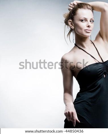 Beautiful Young woman in black dress.  In studio. - stock photo