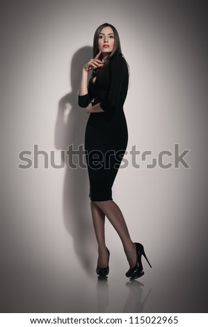 beautiful young woman in black dress on grey