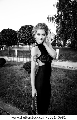 beautiful young woman in black dress on street, black and white photo