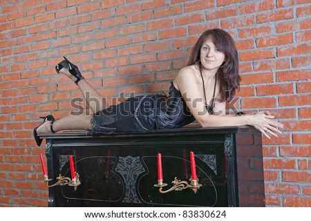 beautiful young woman in black dress sitting on the piano - stock photo
