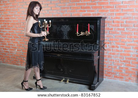 beautiful young woman in black dress stands near the piano - stock photo