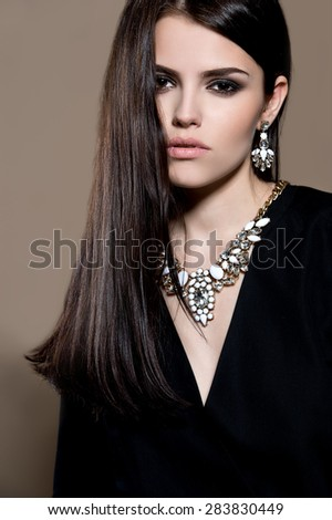 Beautiful young woman in black dress with jewelry. Fashion photo - stock photo